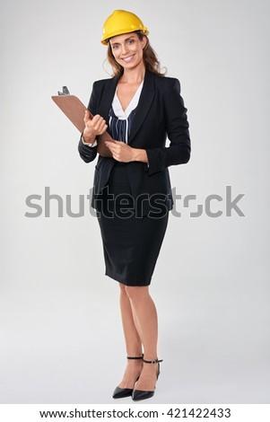 Woman wearing hardhat safety helmet holding clipboard, architect surveyor engineer professional - stock photo