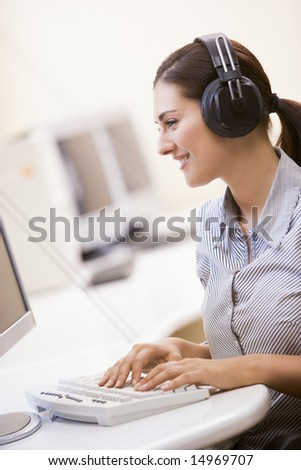 Woman wearing headphones in computer room typing and smiling - stock photo