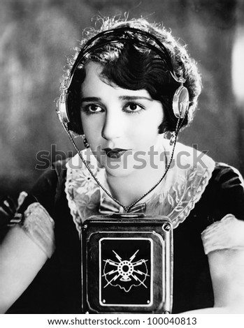 Woman wearing headphones with a microphone in front of her - stock photo