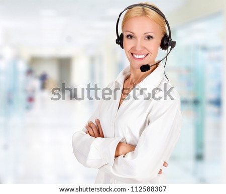 Woman wearing headset in office - stock photo