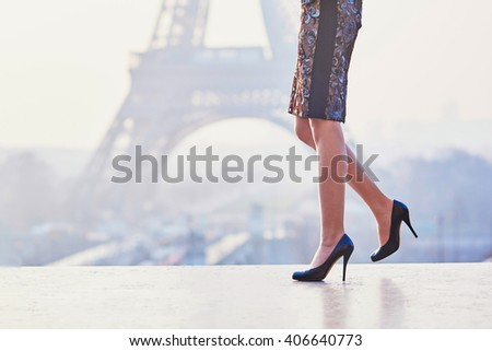 Woman wearing high heels shoes and walking near the Eiffel tower at early morning in Paris, closeup of legs - stock photo