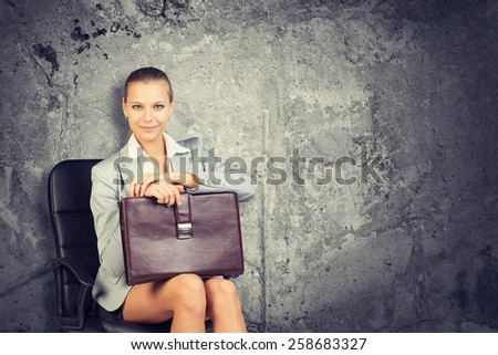 Woman wearing jacket and blouse holding briefcase. Background concrete wall - stock photo