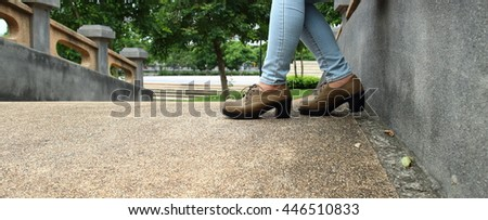 Woman wearing jeans And brown shoes boots Sitting on the bridge Park - stock photo