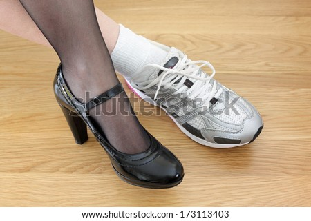 Woman wearing one business shoe and sports shoe concept for work-life balance, healthy lifestyle and wellbeing choice - stock photo
