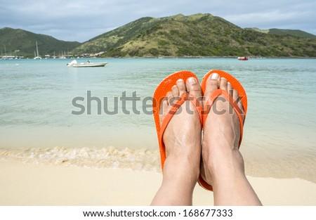 Woman Wearing Orange Flip Flop on the Beach  - stock photo