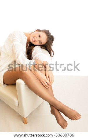 Woman wearing pantyhose sitting in armchair - stock photo