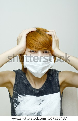 Woman wearing protective mask,Woman with headache holding her hands to the head. - stock photo