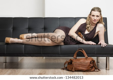 woman wearing pumps with a handbag lying on sofa - stock photo