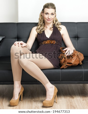 woman wearing pumps with a handbag sitting on sofa - stock photo