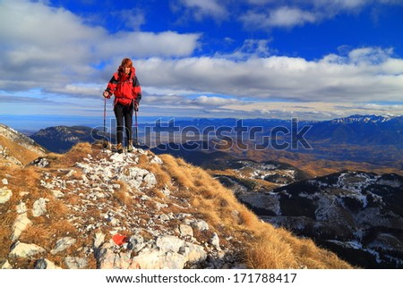 Woman wearing red jacket hikes on the mountain in autumn - stock photo