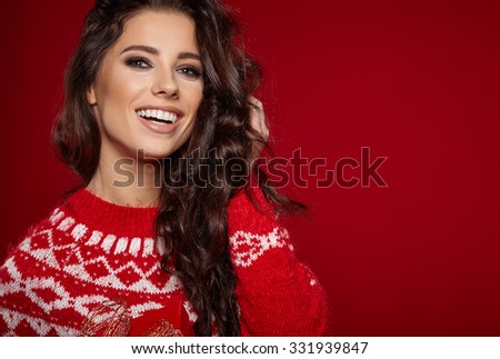 Woman wearing red sweater against red wall background - stock photo