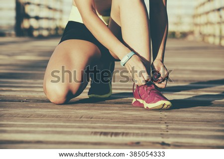 Woman wearing running shoes on the park - stock photo
