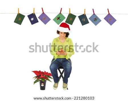 Woman wearing Santa Claus hat  with Poinsettia plant at her feet looking at camera with Christmas cards hanging on wall with clothes pins isolated on white background - stock photo