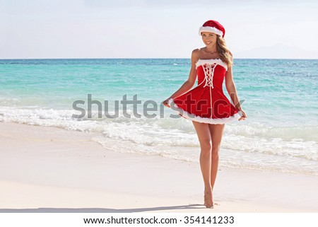 Woman wearing santa claus stylized dress posing on beach - stock photo