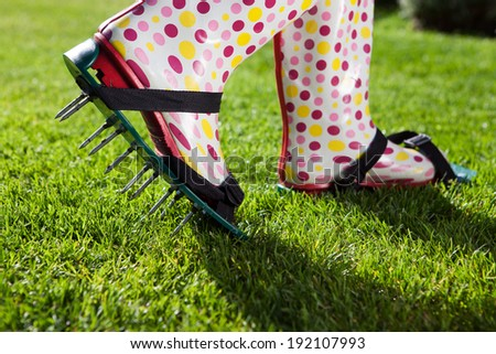 Woman wearing spiked lawn revitalizing aerating shoes, gardening concept - stock photo