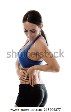 woman wearing sports bra and shorts in pain - stock photo