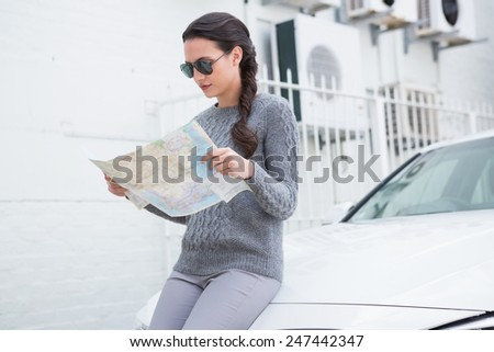 Woman wearing sunglasses reading map beside her car in a car park - stock photo
