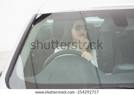 Woman wearing sunglasses using mirror to put on lip gloss in her car - stock photo