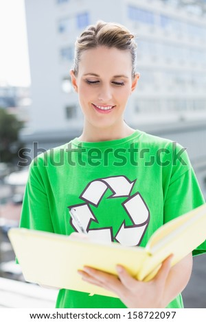 Woman wearing tshirt with recycling symbol holding notebook outside on a sunny day - stock photo