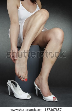 Woman wearing white dress and heel shoes over grey background - stock photo
