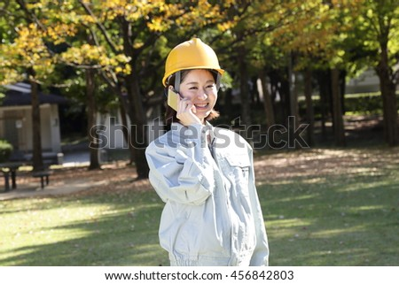 Woman wearing work clothes that are in the park - stock photo