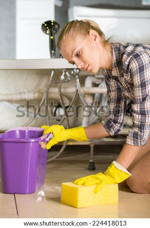 Woman while cleaning the floor in the bathroom. - stock photo