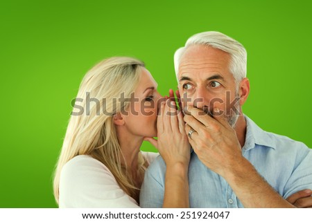 Woman whispering a secret to husband against green vignette - stock photo