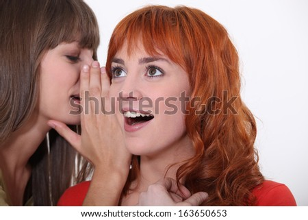 Woman whispering into another woman's ear - stock photo