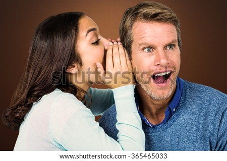 Woman whispering secret with man against shades of brown - stock photo