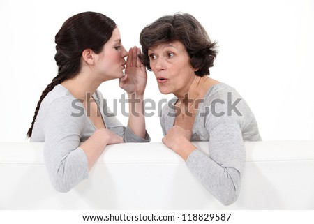 Woman whispering to her mother - stock photo