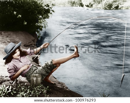 Woman who caught a small fish falling over backwards - stock photo
