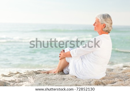 Woman who is sitting on the beach - stock photo