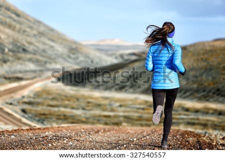 Woman winter and autumn running in down jacket. Female running jogging on mountain trail in beautiful landscape. - stock photo
