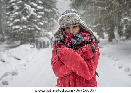 Woman winter hiking. Beautiful young woman enjoying the falling snow dressed in a winter scarf and cap and with a satchel on her back with copyspace. - stock photo