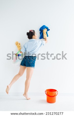 Woman wiping a wall, rear view - stock photo