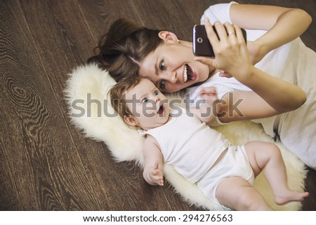 Woman with a baby doing a selfie lying on wooden floor - stock photo