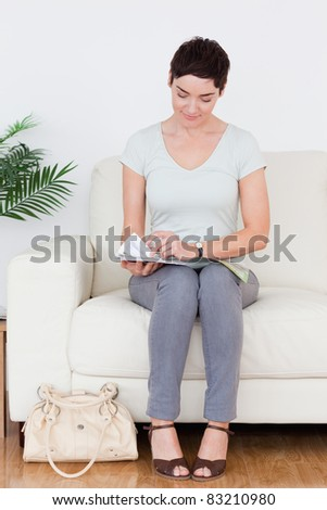 Woman with a bag and a magazine in a waiting room - stock photo
