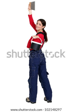 Woman with a bucket of tile adhesive and comb - stock photo
