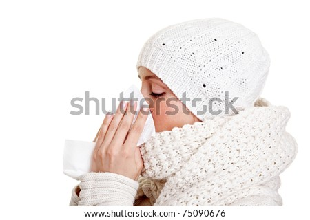Woman with a cold blowing her nose with a handkerchief - stock photo
