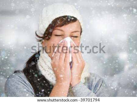 woman with a cold holding a tissue - it's snowing - stock photo