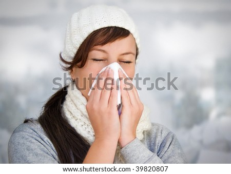 woman with a cold holding a tissue (without snow in background) - stock photo