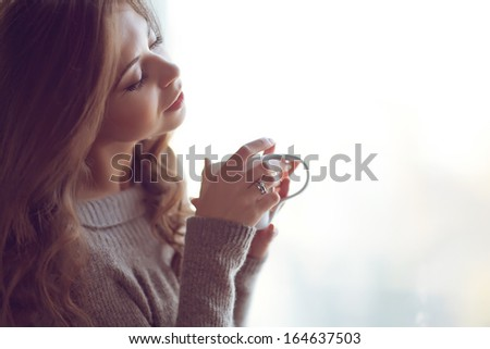 Woman with a cup at the window - stock photo