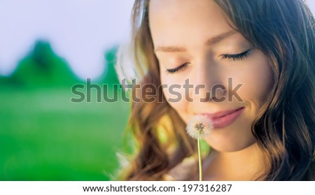 woman with a dandelion outdoor in the summer park, closeup - stock photo