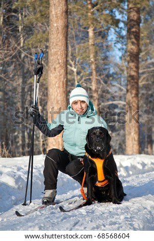 woman with a dog on walking in winter wood - stock photo
