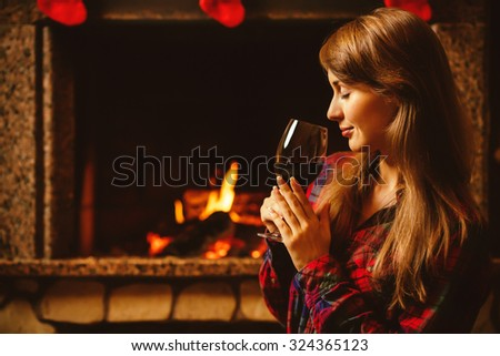 Woman with a glass of wine by the fireplace. Young attractive woman sitting by the fireside and holding a wineglass, enjoying cozy evening. Holiday time concept in a house decorated for Christmas. - stock photo