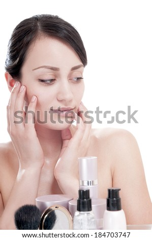 Woman with a good complexion near the creams cosmetics. Skin care concept. - stock photo