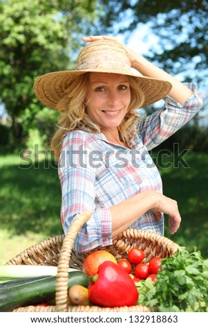 Woman with a hand on her hat and basket of vegetables. - stock photo