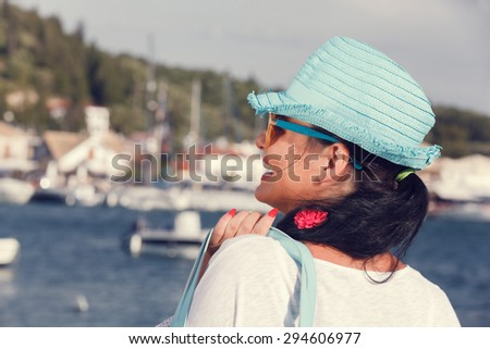 Woman with a hat looking at the sea during sunset. Side  view of a woman wearing a straw hat looking at the sea, near the yacht marine - stock photo