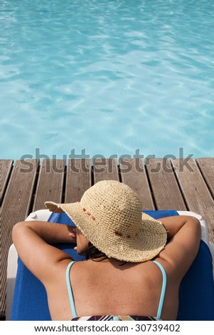 woman with a hat relaxing at the pool - stock photo