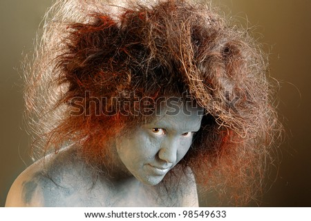 Woman with a painted face and a nest in hair - stock photo